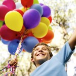 Young Boy Holding a String of Balloons