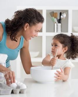 mom daughter mixing bowl eggs